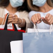 two-defocused-women-with-medical-masks-holding-shopping-bags-with-sale-items